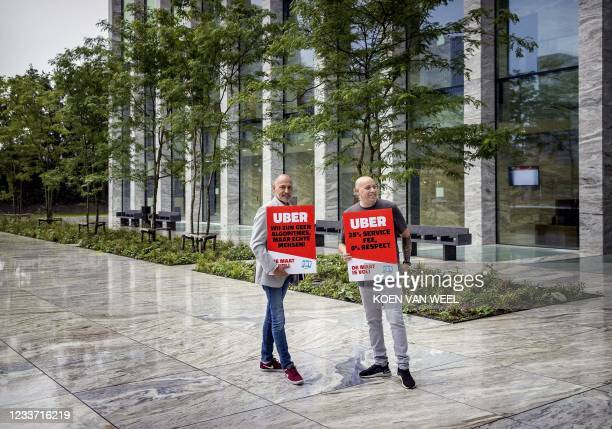 """Drivers of Uber hold a sign saying """"Uber, we are no algorithms, bur real people!"""" in front of the courtroom before the hearing between trade union..."""