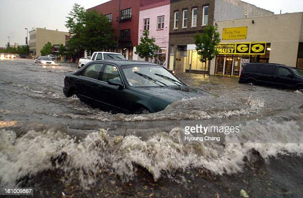 Drivers plow through the deep street flooding at the corner of Alameda and Broadway during the afternoon storm on Sunday