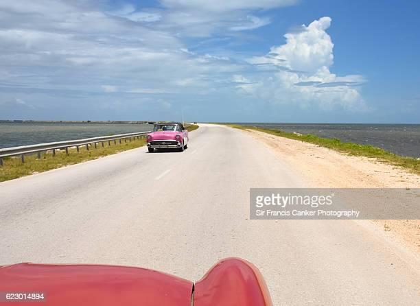Driver's PoV of a vintage car on Caribbean causeway leading to Cayo Santa Maria, Cuba