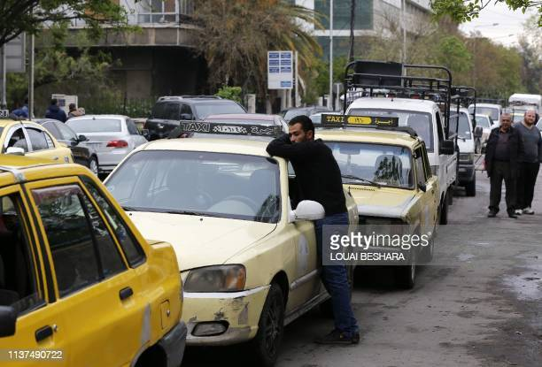 Drivers queue for gasoline in front of a petrol station in the Syrian capital Damascus on April 16, 2019. - Syria adopted new measures yesterday to...