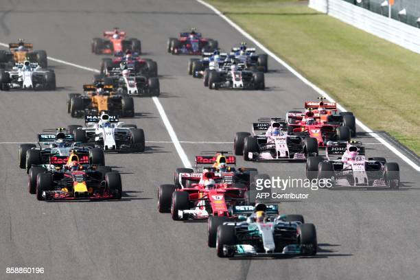 Drivers race off from the starting grid during the Formula One Japanese Grand Prix at Suzuka on October 8, 2017. / AFP PHOTO / Behrouz MEHRI