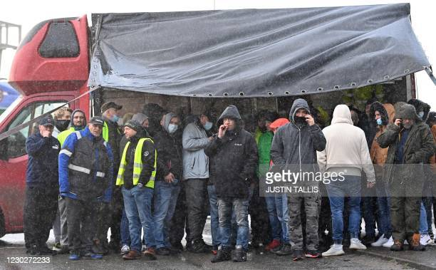 Drivers shelter from the rain by a lorry as they block the road by the entrance to the port in Dover, in Kent, south east England on December 23 as...