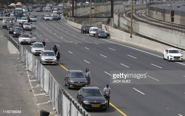 Drivers stop and stand in silence on a highway in the Israeli city of Tel Aviv on May 02, 2019 as sirens wailed across Israel for two minutes marking...