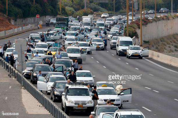 Drivers stop and stand in silence on a highway in the Israeli city of Tel Aviv on April 12 2017 as sirens wailed across Israel for two minutes...
