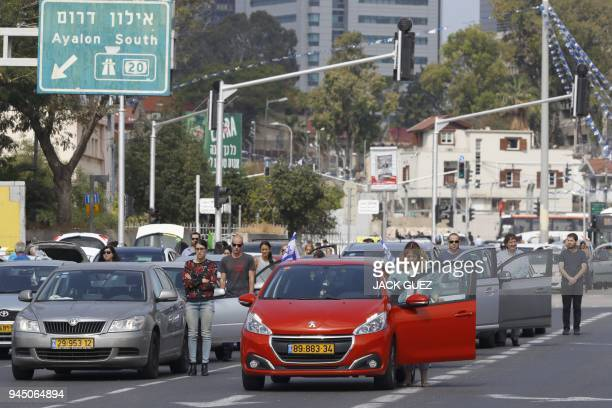 Drivers stop and stand in silence on a street in the Israeli city of Tel Aviv on April 12 2017 as sirens wailed across Israel for two minutes marking...