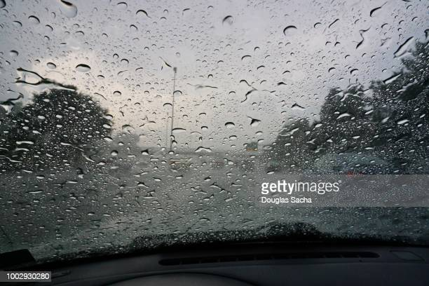 drivers view of a moving car on a rainy day - lluvia torrencial fotografías e imágenes de stock