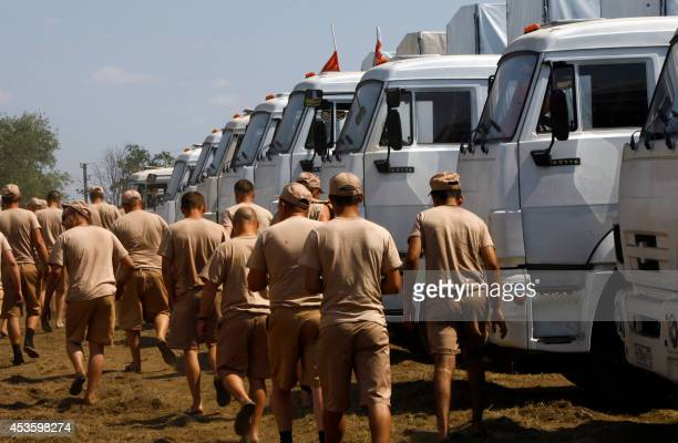 Drivers walks past the Russian humanitarian convoy trucks parked on a field outside the town of KamenskShakhtinsky in the Rostov region some 30kms...