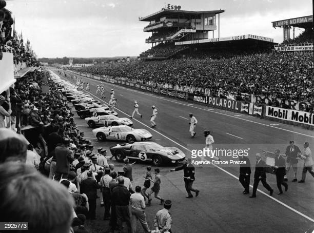 Drivers wearing helmets run to their cars after the commencement of the 24 Hour Le Mans Auto race France June 18 1966
