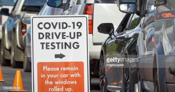 「covid-19ドライブアップテスト」サインはフォアグラウンドに座り、車やその他の車両はドライブアップ(ドライブスルー)covid-19(コロナウイルス)屋外外の検査ライン(セカンドウェーブ)をバッ - 医療検査 ストックフォトと画像