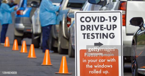 """a """"covid-19 drive-up testing"""" sign sits in the foreground while two female nurses wearing gowns and surgical face masks talk to patients in their cars in a drive-up (drive through) covid-19 (coronavirus) testing line outside a medical clinic/hospital outd - medical test stock pictures, royalty-free photos & images"""