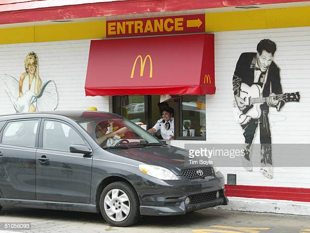 A driveup window customer collects their order between a wall mural of Marylyn Monroe and Chuck Berry at the 'Rock 'N' Roll McDonald's' July 13 2004...