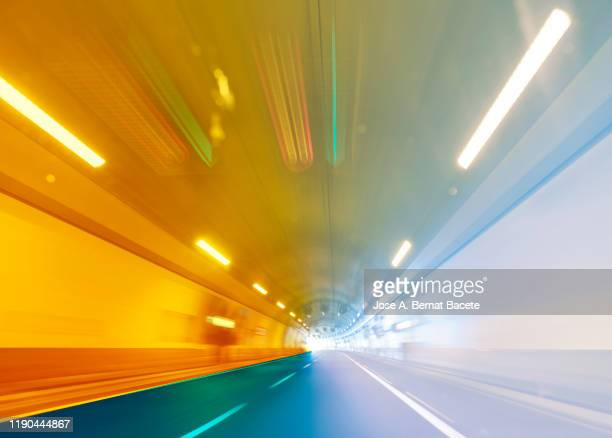 driving a car at high speed inside of an illuminated tunnel. - 境界線 ストックフォトと画像
