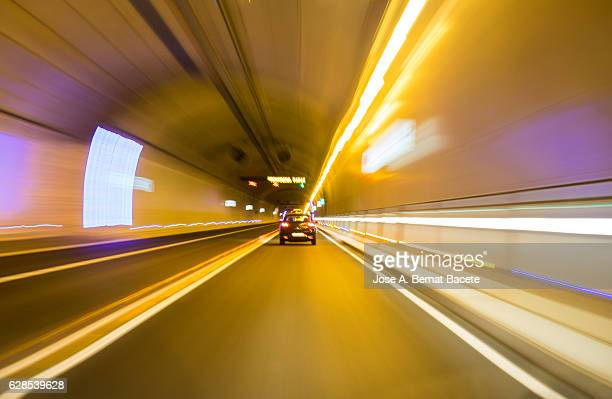 Driving a car at high speed inside of an illuminated tunnel