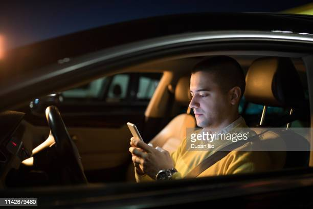 driving and using mobile phone - one man only stock pictures, royalty-free photos & images