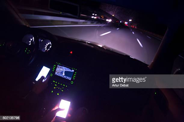 Driving at night in the highway and checking the bright smartphone screen.