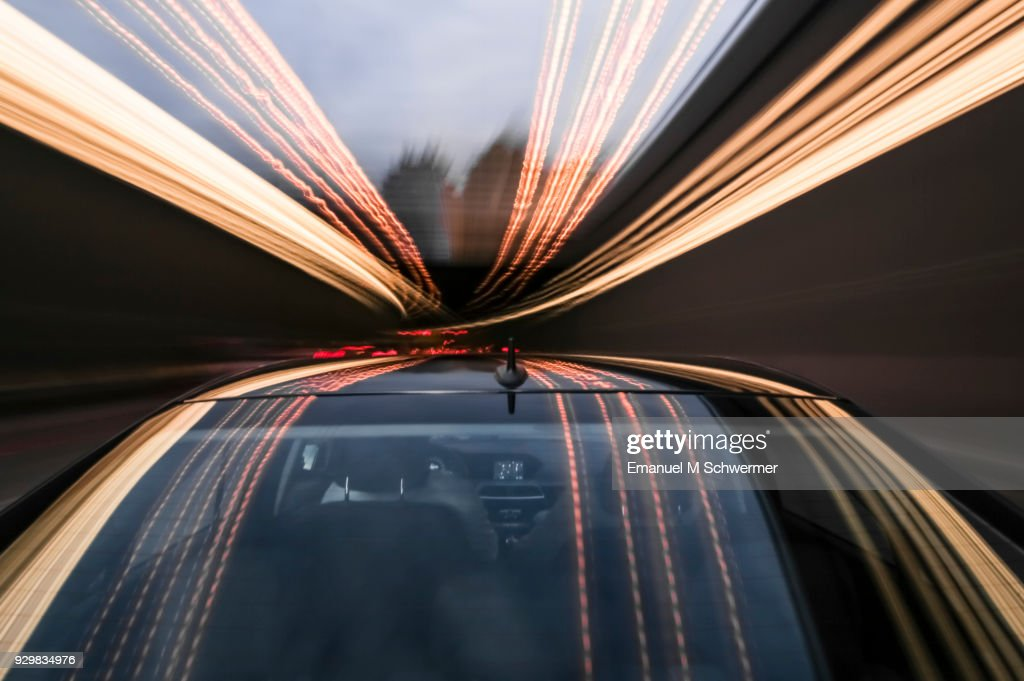 driving black German car with reflections and the rear window in foreground : Stock Photo