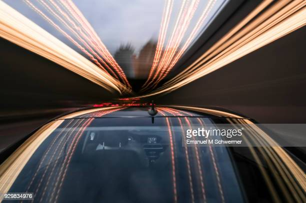 driving black german car with reflections and the rear window in foreground - licht stock-fotos und bilder