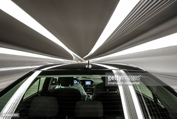 driving black german car with reflections and the rear window in foreground - tunnel - motor vehicle stock pictures, royalty-free photos & images