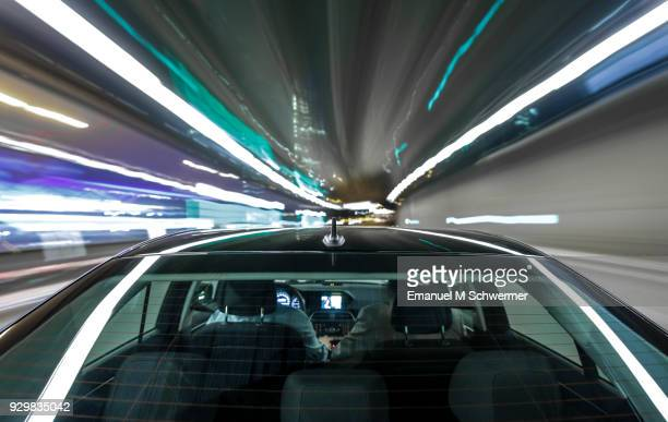 driving black German car with reflections and the rear window in foreground - tunnel-view
