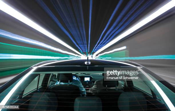 driving black German car with reflections and the rear window in foreground - Tunnel