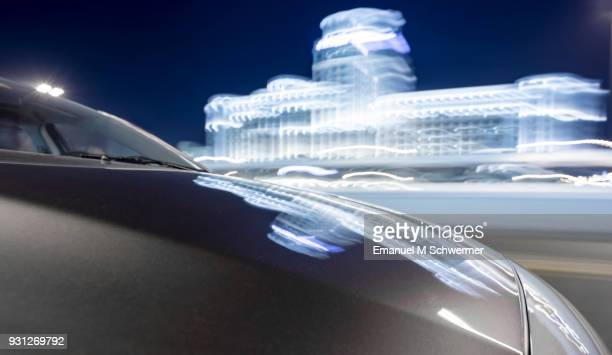 driving car in Dubai while night with illuminated blurred building in background