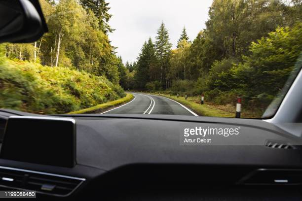 driving in mountain road with wet asphalt and curve from passenger view. - scenics stock pictures, royalty-free photos & images