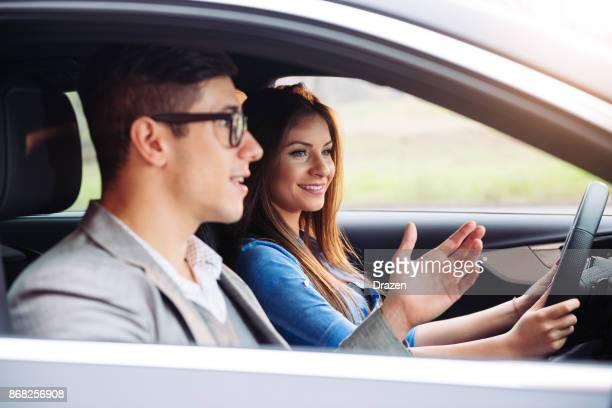 Ausbilder und Auszubildende im Auto im Verkehr fahren