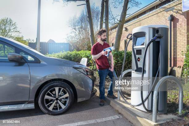 driving instructor charging electric car at car park charging point - elektroauto stock-fotos und bilder