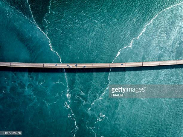 driving on a bridge over deep blue water - bridging the gap stock pictures, royalty-free photos & images