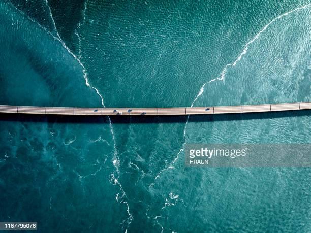 condução em uma ponte sobre a água azul profunda - estabelecer uma ponte - fotografias e filmes do acervo