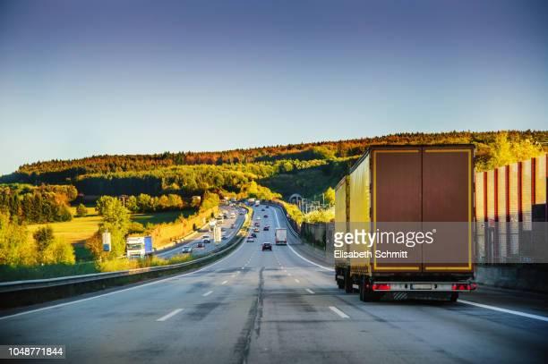 """driving on a freeway / motorway / """"autobahn"""" at sunset - lkw stock-fotos und bilder"""