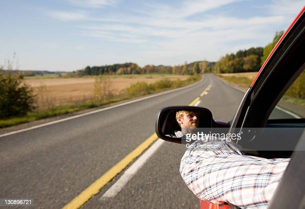 Driving on countryside road with arm out of window