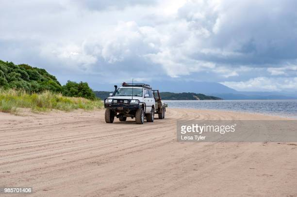 HEADS STRAHAN TASMANIA AUSTRALIA A 4WD driving on the beach near Hell's Gate the entrance to Macquarie Harbour in Tasmania It is a notoriously...