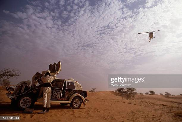 Driving partners Smulevini and Lenorman repair their damaged car a Peugeot 205 T16 in the Mauritanian desert during the 1990 Paris Dakar Rally...