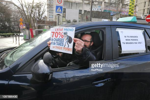 A driving school manager holds a placard reading « Government takes 70% of charges and taxes on each driving license » on Place d'Italie in Paris on...