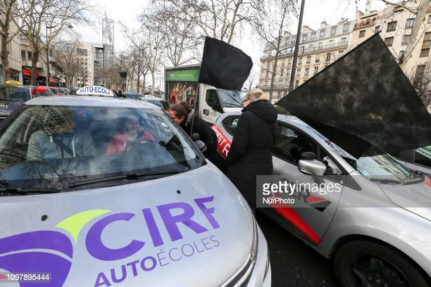 Driving schools managers hold black flags Place d'Italie in Paris on February 11 as they protest against a parliamentary report which could favour...