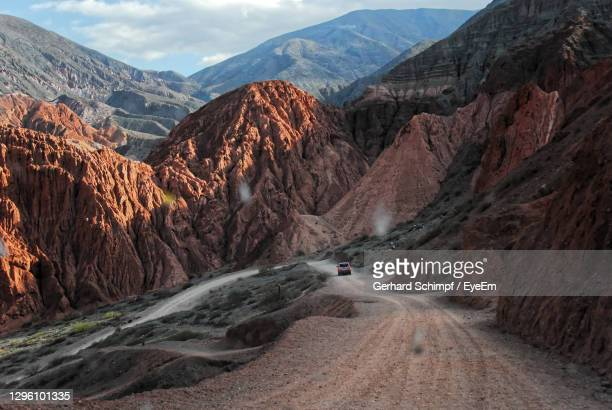 driving through on road through colored mountains near purmamarca argentina - gerhard schimpf stock pictures, royalty-free photos & images