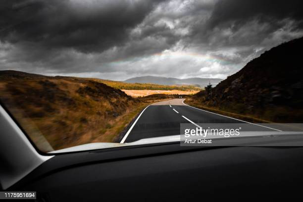 driving through the scottish highlands road with overcast sky and rainbow. - road stock pictures, royalty-free photos & images