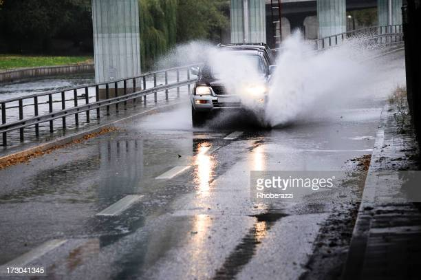 A SUV driving through the water on rainy days