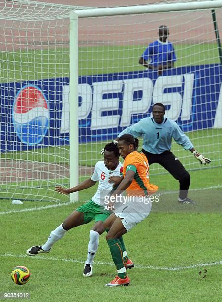 Drogba Didier of 'The Elephants' the Ivory Coast's national football team vies with Kone Bakary and a goalkeeper Dikite Daouda of Burkina Faso on...