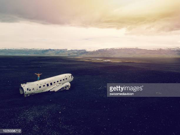 drone aerial view of young man stands arms outstretched on airplane crashed on black sand beach looking around her contemplating surroundings - crash photos stock photos and pictures