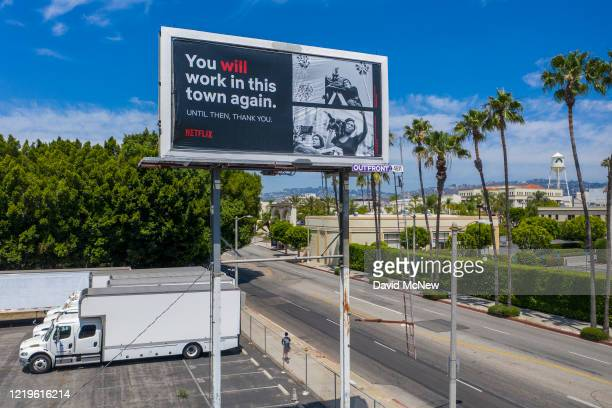 Drone aerial view shows a billboard offering hope to out of work members of the film industry, near idled film trucks and Paramount Pictures Studios...