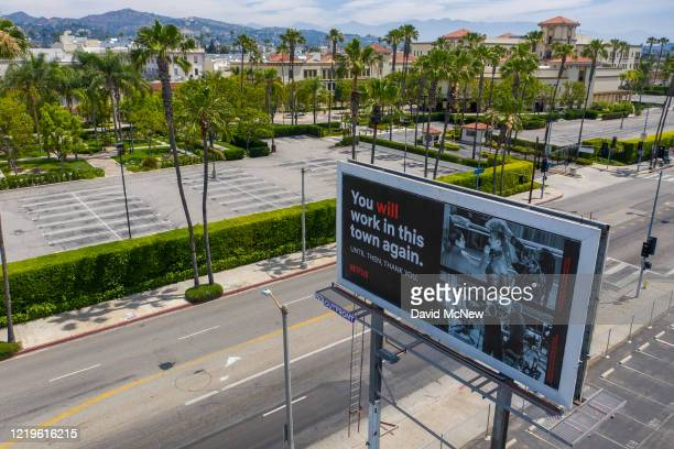 Drone aerial view shows a billboard offering hope to out of work members of the film industry, near vacant parking lots of Paramount Pictures Studios...