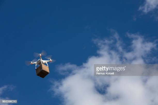 Drone delivering a cardboard box on a blue sky.
