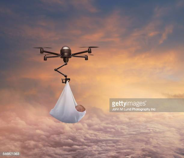 Drone delivering newborn baby in sunrise sky