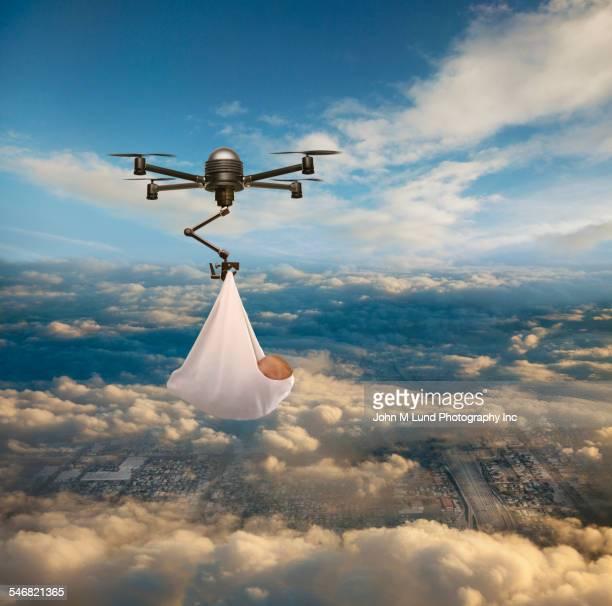 Drone delivering newborn baby over cityscape