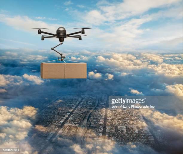 drone delivering package over cityscape - drohne stock-fotos und bilder