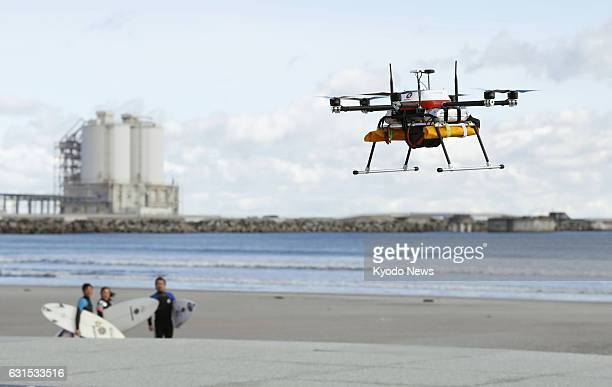 A drone delivers a bottle of hot soup to surfers on the beach of Minamisoma in the northeastern Japan prefecture of Fukushima on Jan 12 during a test...