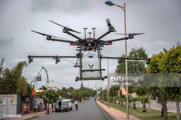 Drone equipped with disinfectant liquid, operated by a Moroccan startup company, is flown above a street of Harhoura near the capital Rabat on April...