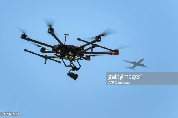 A drone flies as an airplane is seen in the background during a press presentation of Swiss disaster dog association Redog on combined search and...